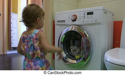 The little kid starts washing machine in the bathroom. HD.