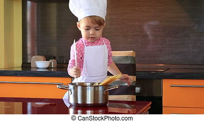 little cute girl in chef suit in the kitchen helping her mother cook spaghetti