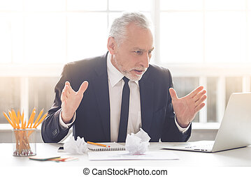 Handsome mature businessman in classic suit is using a...