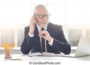 Handsome mature businessman in classic suit and eyeglasses...