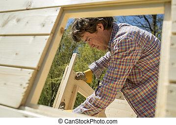 Carpenter building a wooden outdoor hut