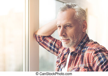 Handsome mature man in casual clothes is looking out the...
