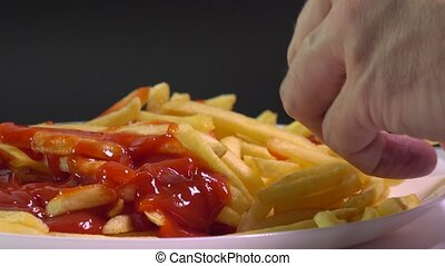Female and male hands picking french fries and dipping them...