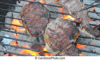 flipping steak on charcoal bbq - steak being flipped over on...