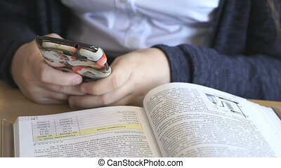 Schoolgirl looking at photos using a mobile phone - The...