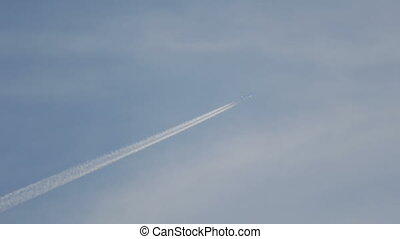 Airliner flying high - Contrails in the blue sky. Airplane...