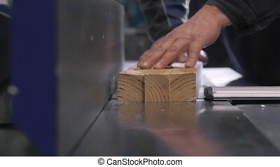 Man Using a Table Saw to cut wood, grinding on modern...