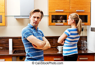 Quarreling couple standing in kitchen and don't talking with...