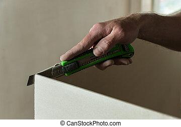 Man cuts a piece of drywall