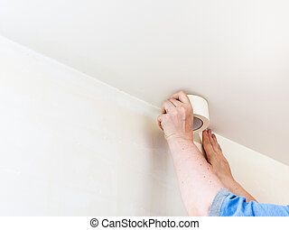 Decorator fixes tape on wall before painting - renovation of...