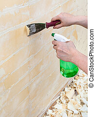 Removing of wet old wallpaper with metal spatula -...