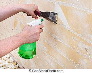 Cleaning wall from wet old wallpaper with spatula -...