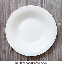 top view of white deep plate on gray brown table - top view...