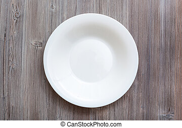 above view of white deep plate on gray brown table - above...