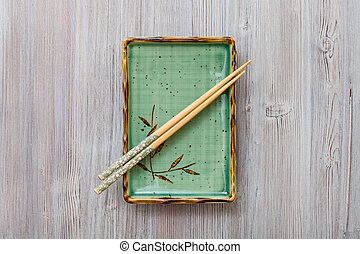 above view of square plate with chopsticks on gray - top...