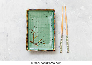 top view of green plate and chopsticks on concrete - top...