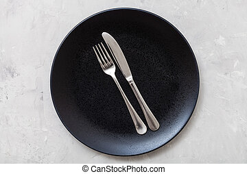 top view of black plate with flatware on concrete - food...