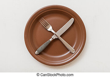 top view of brown plate with cultery on white - food concept...