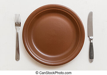 top view of brown plate with knife, spoon on white - food...