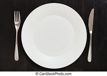 top view of white plate with knife, spoon on dark - food...
