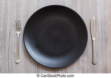 top view of black plate with knife, spoon on gray - food...