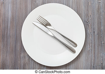 top view of white plate with flatware on gray - food concept...