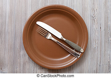 top view of brown plate with flatware on gray - food concept...