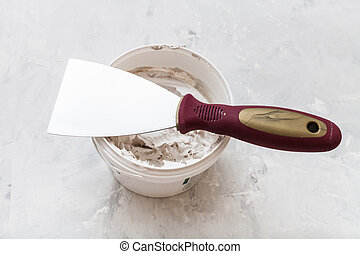 metal spatula on tube with putty - metal spatula with...