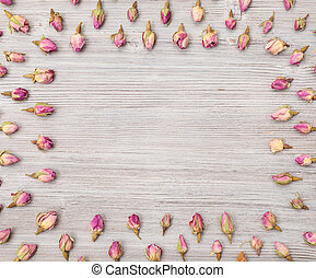 frame from rose flower buds on wooden plank