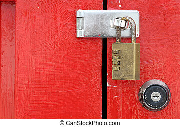 wooden red door with padlock - closeup of old wooden red...