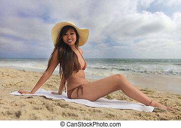 Woman on the Beach in a Bikini Sitting