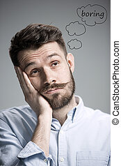 Man is looking bored. Over gray background - Man wearing a...