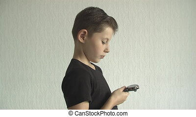 Young boy checking his  for the time on his wrist watch.
