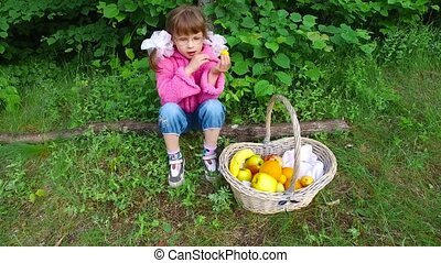 Girl child eats apricots in summer forest. The girl has a good appetite in the fresh air. Fruits are very tasty. Summer evening in the forest.