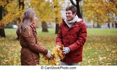 happy young couple throwing autumn leaves in park