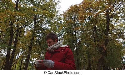 young man with smartphone walking at autumn park -...