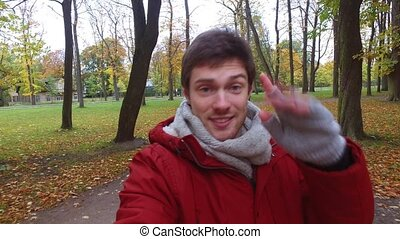 man with smartphone taking video at autumn park -...
