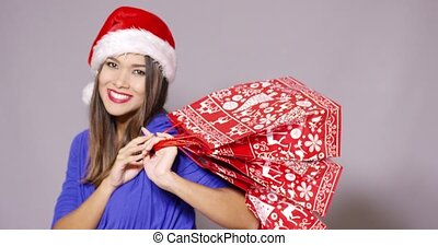 Friendly young woman with Christmas shopping bags - Friendly...