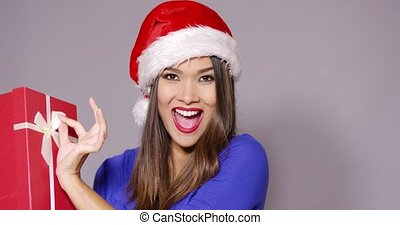 Excited woman in a Santa hat holding a gift - Excited...