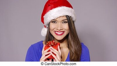 Gorgeous woman in Santa hat holding gift - Gorgeous smiling...