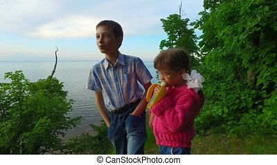 Children have a rest in the forest on the banks of a large lake. Girl child eats a banana. Boy teenager tells his story. Evening in the summer forest. The sun hid behind the clouds.