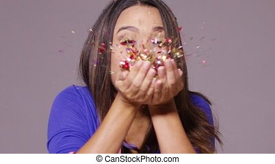 Cute young woman blowing confetti at the camera from the...