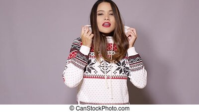 Cute young woman in warm cozy winter fashion snuggling into...