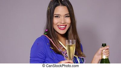 Gorgeous young woman celebrating with champagne holding an...