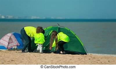 Mom daughter and son go in the green tent on the beach. -...
