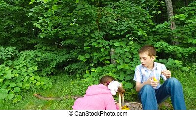 Children have a rest in the forest. Evening meal in the forest fruits. Boy teenager eating apricot. Child girl tells how good to eat fruit in the forest. Summer evening forest. Cloudy weather.