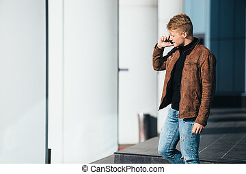Young man talking on the phone, using smartphone, making a call.