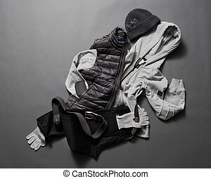 Collection of men's warm clothes on a dark background....