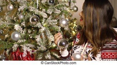 Pretty woman decorating an Xmas tree with baubles smiling as...
