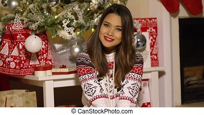 Gorgeous young woman enjoying Christmas posing in her living...